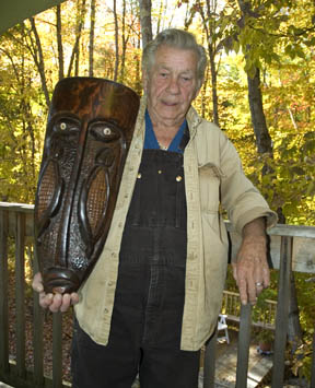 Joseph Johns, aka Cayoni, with one of his woodcarvings.