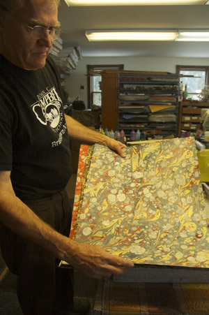 Dan holding sheet of marbled paper