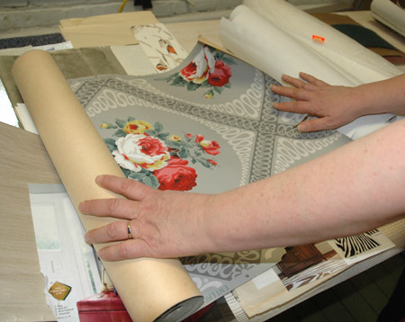 Rolling out a sample of wallpaper