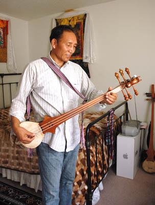 Penpa Tsering playing the he Tibetan pi-wang (lute), Tibetan musician, 2014 Photography by Maggie Holtzberg