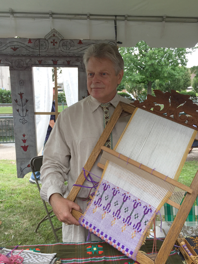Jonas Stundzia holding a frame with Lithuanian pick-up weaving