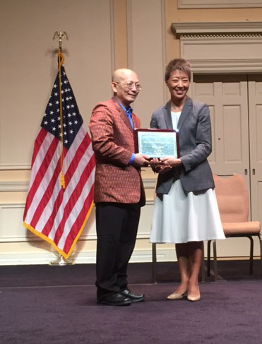 Yary Livan receiving National Heritage Award, posing with NEA Chairwoman Jane Chu