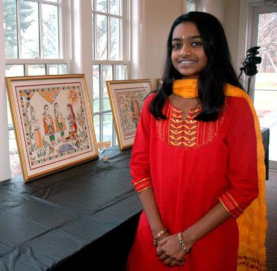 Sanjana Krishnan standing with two of her Madhubani paintingsher