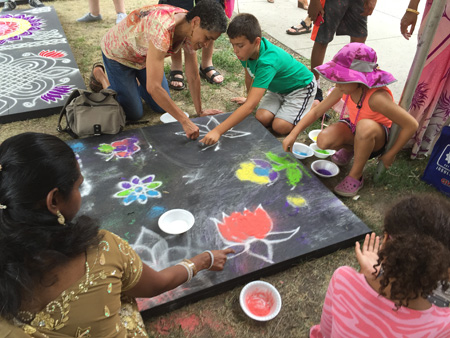 Festival goers trying their hand at making kolam