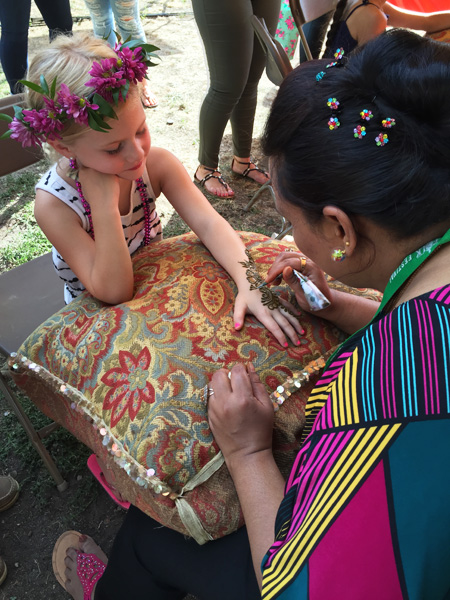 Noureen Sultana applying henna to child
