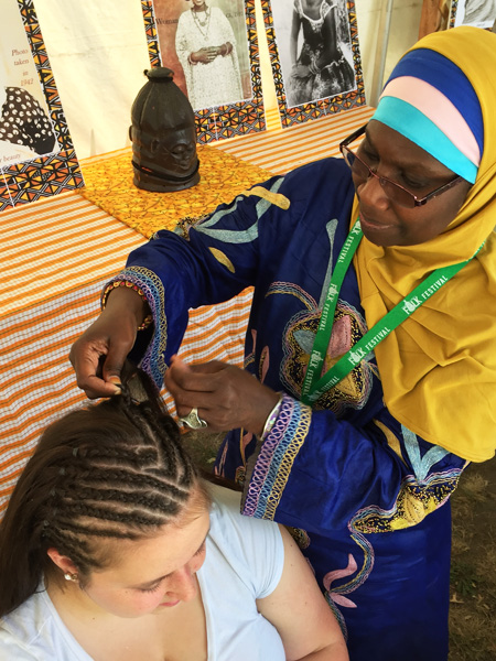 Sellou Coly braiding a young worman's hair